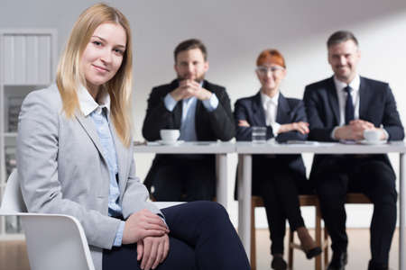 Corporations: Young woman hired in big corporation. In the background pleased smiling employers behind table