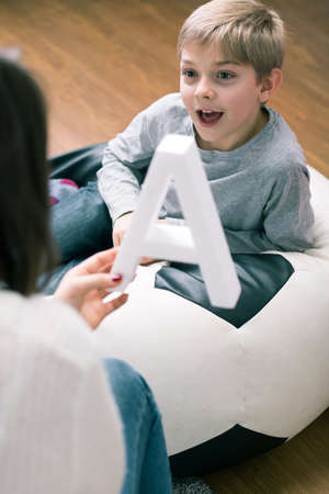 Pedagogue helping little boy to learn new letters. Woman holding big letter a and happy boy next to her Reklamní fotografie