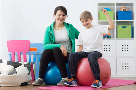 faulty: Content boy and woman instructor sitting on gym balls. Stock Photo
