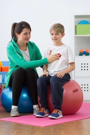 body posture: Physiotherapist correcting body posture of a boy sitting on gym ball. Stock Photo