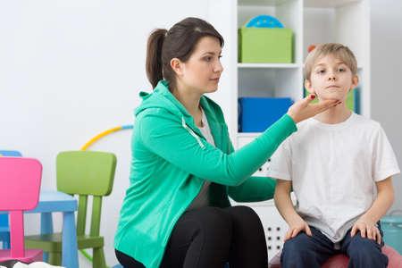 body posture: Woman phsyiotherapist correcting boys body posture during exercises.