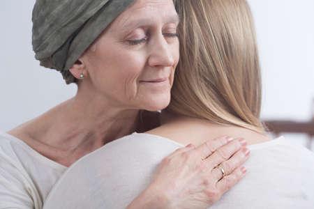 apoyo familiar: Mujer enferma con cáncer que abraza a su pequeña hija
