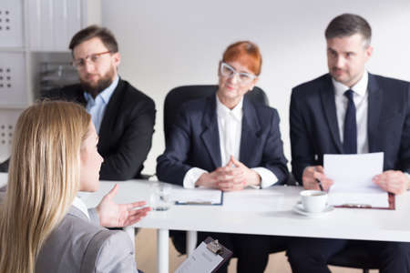 intern: Young pretty intern talking with three bossy businesspeople to work in company