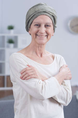 bald: Portrait of senior woman in scarf on head with cancer in good humor