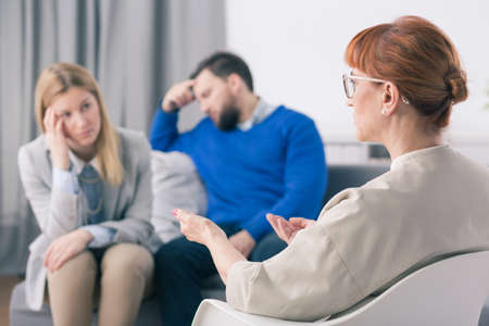 young wife: Senior psychologist trying to find solution for young coupes problems. Broken down man and his worried wife sitting on couch