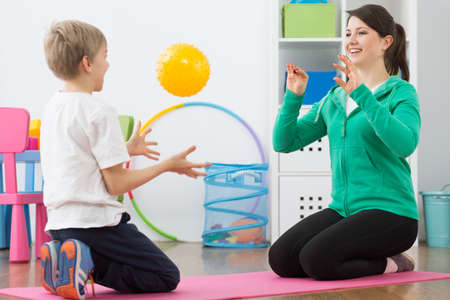 child smile: Woman and boy playing ball in rehabilitation room.