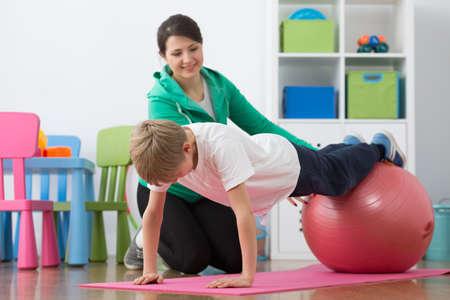 Jongen tijdens fysiotherapie oefeningen op gymnastiekbal en vrouw instructeur.