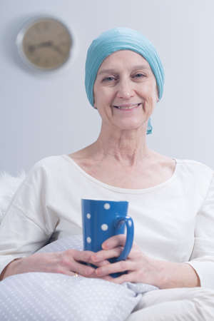 fight disease: Older smiling positive woman with scarf on head after chemotherapy relaxing at home with cup of tea
