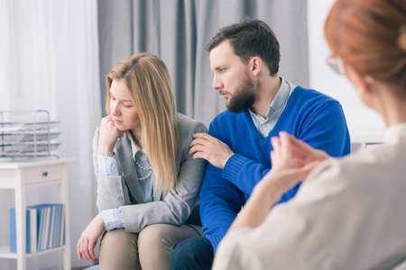 young wife: Young marriage in separation at psychotherapists office. Man cheering up his wife