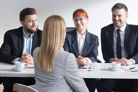 Three corporation employers happy of hiring new young blonde applicant