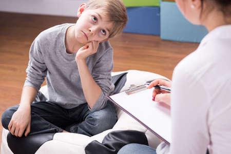 El niño pequeño aburrido de la conversación con el joven psicólogo durante la psicoterapia