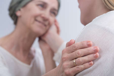 fight disease: Young woman touching her sick mothers cheek. Older woman with scarf on head sick on cancer