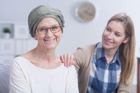 donna innamorata: Anziano, donna sorridente con la sciarpa sulla testa in lotta con il cancro con le sue figlie aiutano Archivio Fotografico