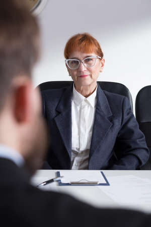 bossy: Older bossy woman in suit in corporation talking with young applicant Stock Photo