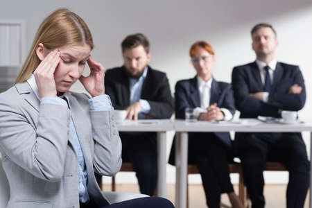 employers: Stressed young woman before job interview and three bossy employers waiting for her