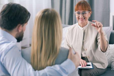 matrimonio feliz: Mayor que sonríe feliz psicólogo de los resultados de su terapia matrimonio con la joven pareja