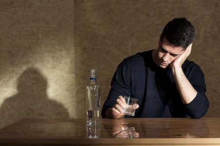 beside table: Man sitting beside table, holding glass, bottle of vodka on table