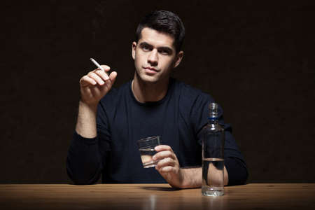 people shadow: Man holding cigarette and glass, bottle of vodka on the table, dark background