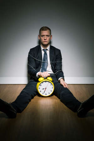 young businessman: Young corporation employer forced to work after hours. Man sitting in chains and holding alarm clock