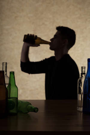 the drinker: Shadow of man holding bottle, drinking, empty bottles next to him