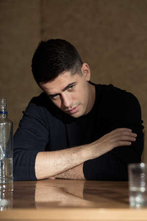 beside table: Young man sitting beside table, bottle of vodka and glass next to him