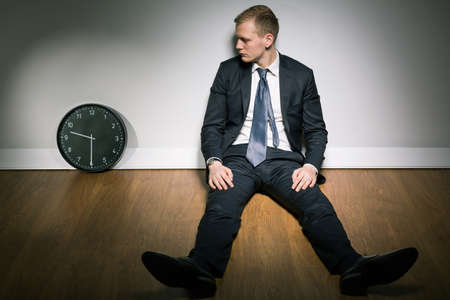 the passing of time: Concerned young man in suit looking at passing time on clock