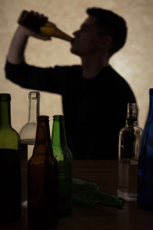 the drinker: Shadow of man drinking alcohol, surrounded by empty bottles Stock Photo