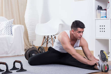 tight fit: Active man stretching body after workout