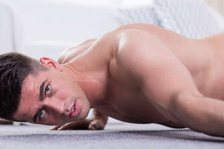 muscled: Young muscled man training at home without shirt