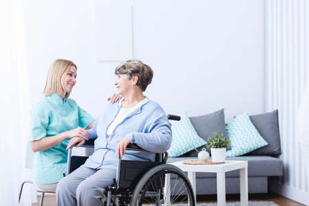health care: Photo of senior lady on wheelchair and her caregiver Stock Photo