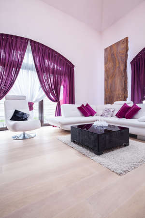 view of a spacious living room: Purple living room with white leather lounge suite Stock Photo