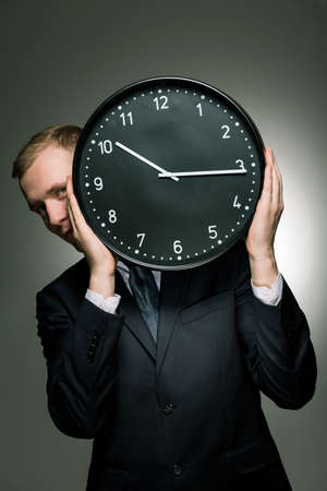 haste: Young businessman in suit holding big clock. Living in permanent haste