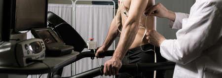 Fotografía recortada de un médico de comprobación de electrodos en el cuerpo de su paciente