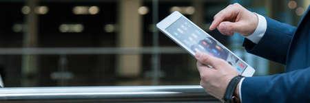 personas trabajando: Primer plano del hombre en traje de trabajo en su nueva tableta. Primer plano de las manos del hombre que sostiene el dispositivo Foto de archivo
