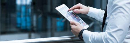Primer plano del hombre en juego usando la nueva tableta para el trabajo. De pie en el cargo en la compañía