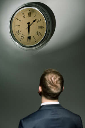 under pressure: Young businessman under pressure looking at watch with fast passing time