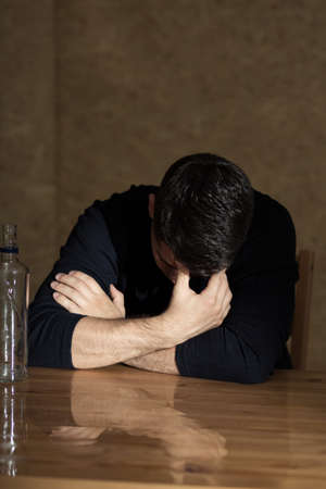 beside table: Man holding head down, sitting beside table