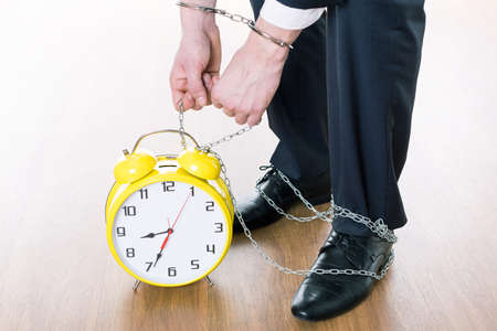 the passing of time: Close-up of businessmans legs chained to big alarm clock with passing time
