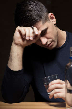 vodka bottle: Man holding head on his hand, smoking and drinking vodka, bottle on table, dark background Stock Photo