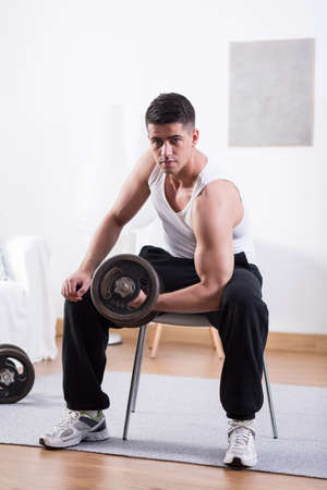 muscled: Muscled young man lifting heavy dumbbell at home