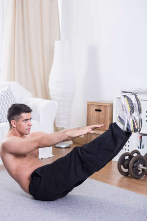 crunches: Strong young man doing crunches on floor