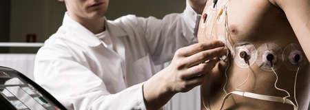 Disparo de un médico de comprobación de electrodos en el cuerpo de su paciente