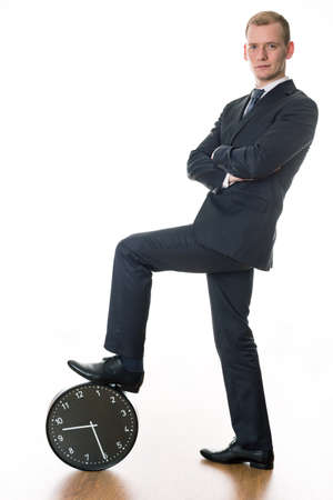 after hours: Confident young businessman ready to work in the morning. Holding his foot on big clock Stock Photo