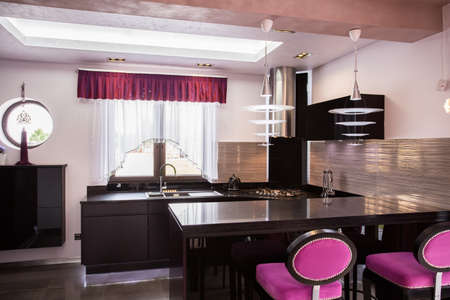 violet residential: Dark kitchen furniture with purple chairs and decorations