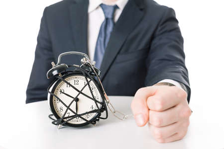 the passing of time: Close-up of angry mans fist imprisoned to alarm clock. Feeling passing time pressure Stock Photo