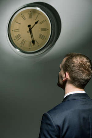 after hours: Young businessman in suit looking at ticking clock hanging on wall