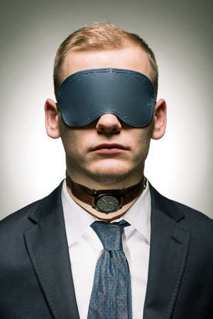 after hours: Young employer of corporation in suit with band on eyes and watch on his neck Stock Photo
