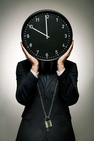 the passing of time: Elegant man in suit imprisoned by passing time. Big clock instead of mans head Stock Photo