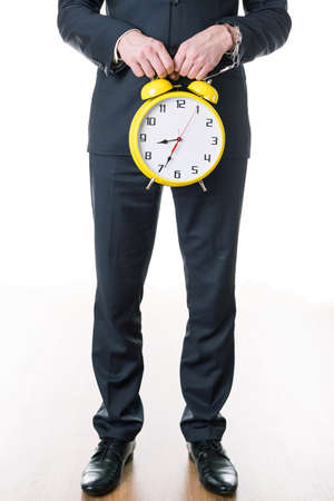 after hours: Close-up of young businessman in suit ready to work holding alarm clock. Mans hand in handcuff chained to watch Stock Photo