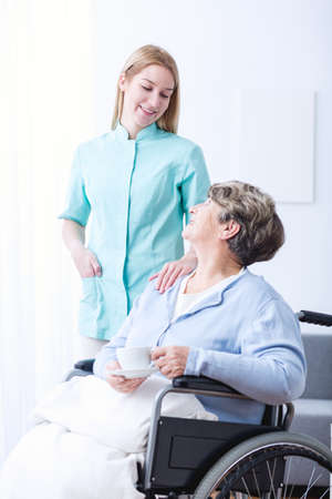 afflictions: Image of elderly female on wheelchair with carer Stock Photo